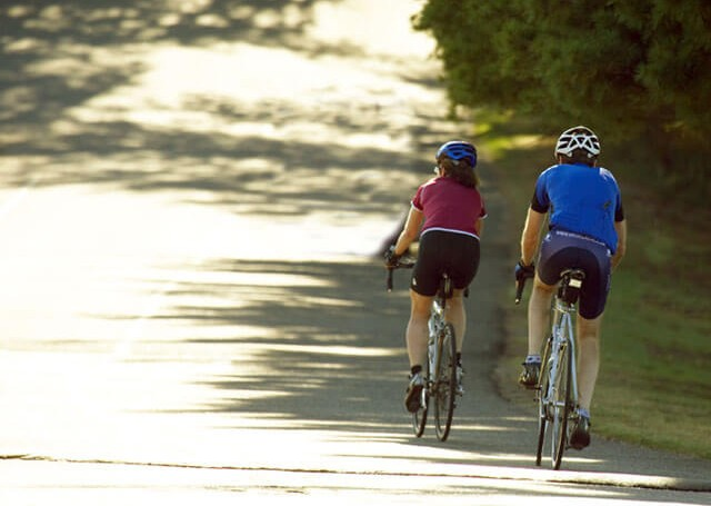 Couple cycling on side of road