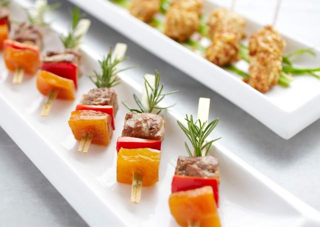 Meat shish kebabs on white plates