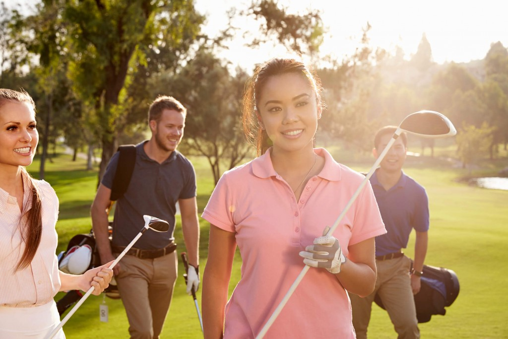 group of two men and two women holding golf clubs and standing in sun, smiling