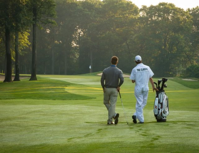 Rear view of a guest playing golf on the course