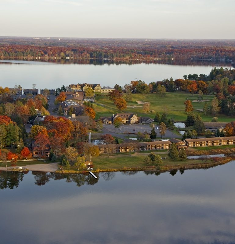 Stunning aerial view of Madden's on Gull lake in the fall with still waters and trees with changing leaves