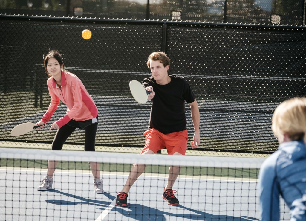 A group of young people playing the game of pickleball on a court.