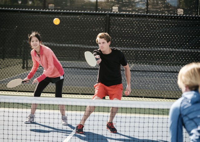Couple playing pickleball outdoors on a court