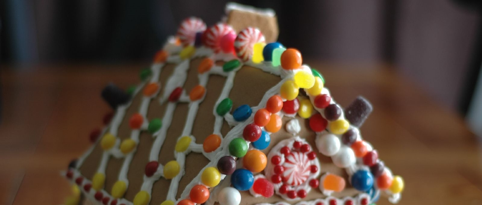 Macro photo of colorfully decorated gingerbread house adorned with candies of various types
