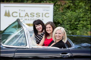 Three women in car next to sign for the Classic at Madden's on Gull Lake