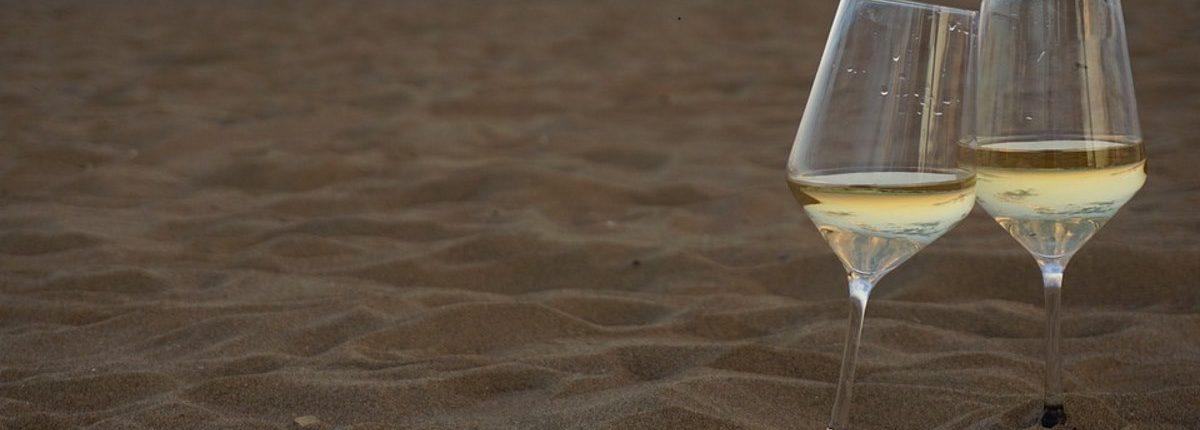 Crisp white wine in wine glass on a beautiful sand beach