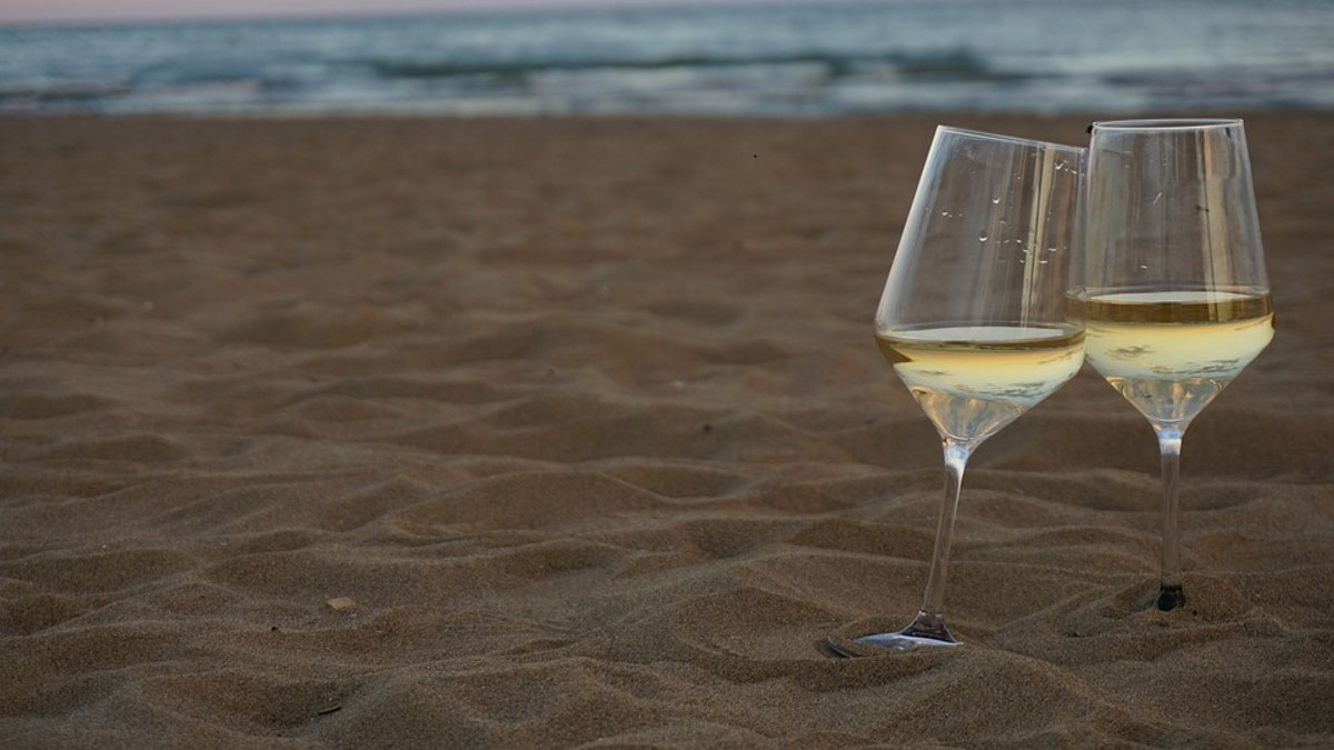 Crisp white wine in wine glass on a beautiful sand beach