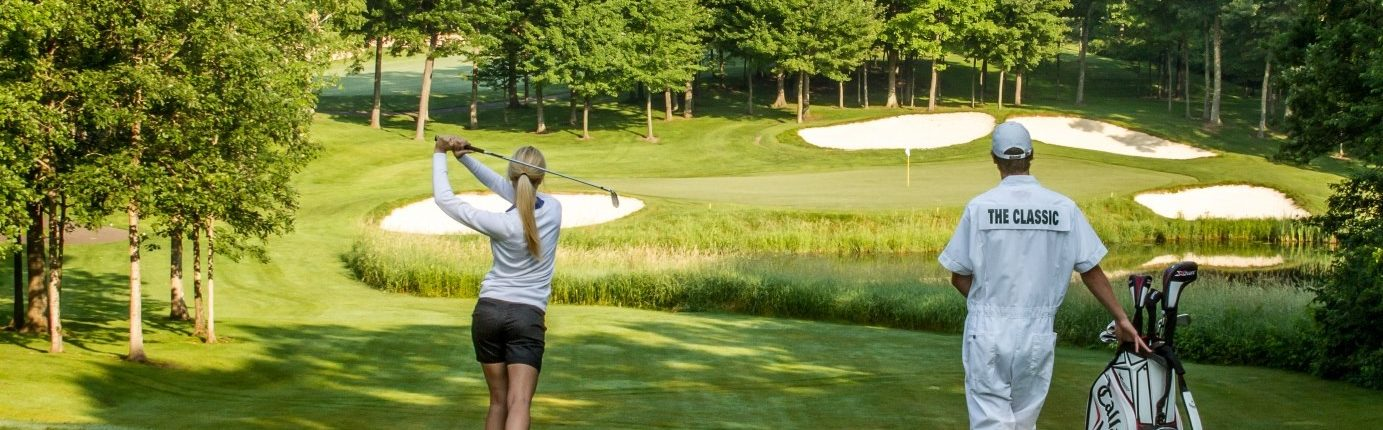 Woman taking golf swing at the Classic golf course at Madden's on Gull Lake