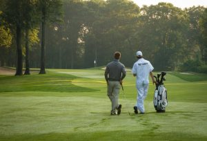 Golfer and his caddy at Maddens leaning on golf club admiring the Classic Golf course