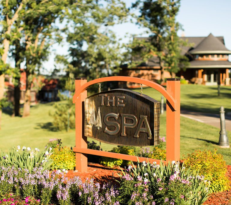 The Spa at Maddens sign in colorful garden on a sunny day.