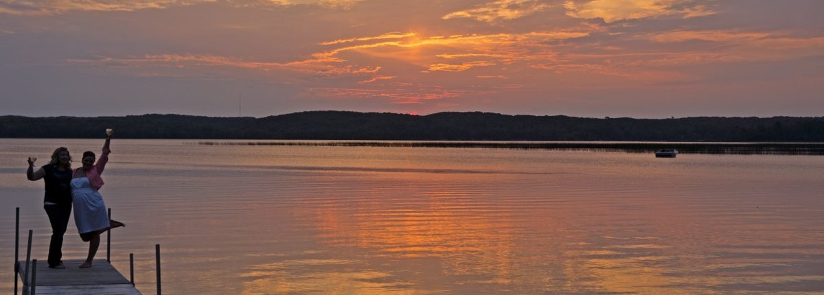 Breathtaking sunset of orange and pink skies over the lake at Wilson Bay