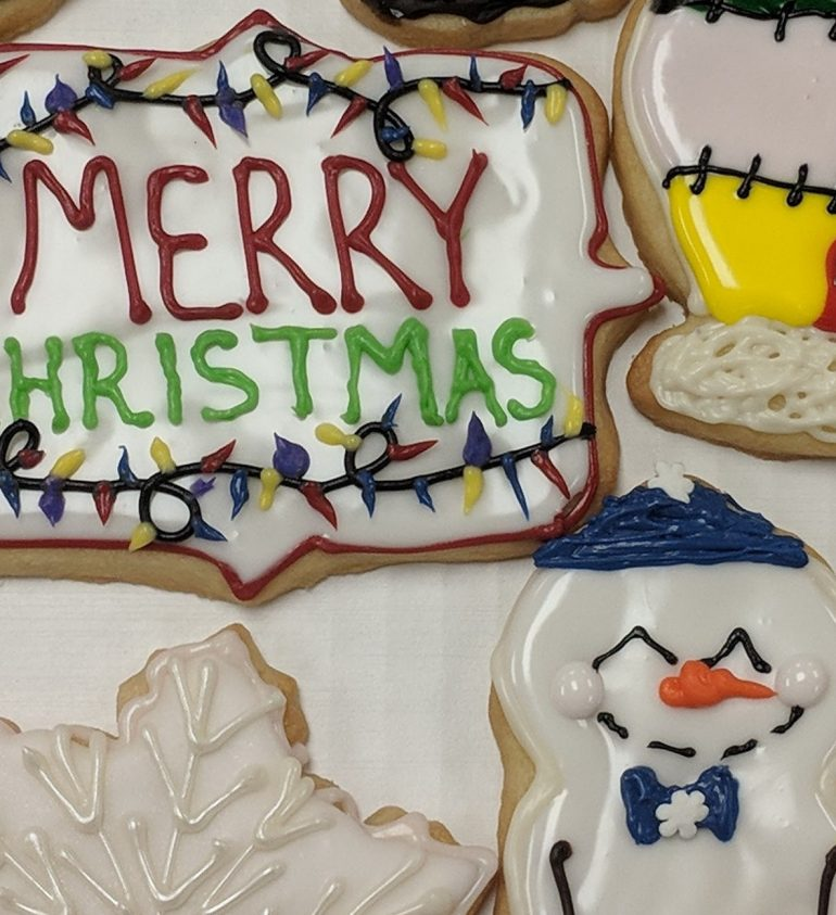 Festive Sugar Cookies beautifully decorated with icing reading Merry Christmas