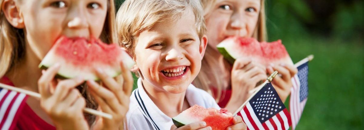 Children eating watermelon slices while holding their miniature American flags.