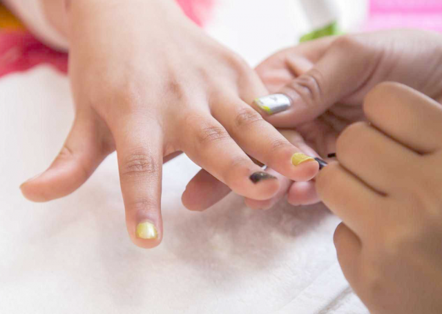Aesthetician's hand applying nail polish on the guest's nail