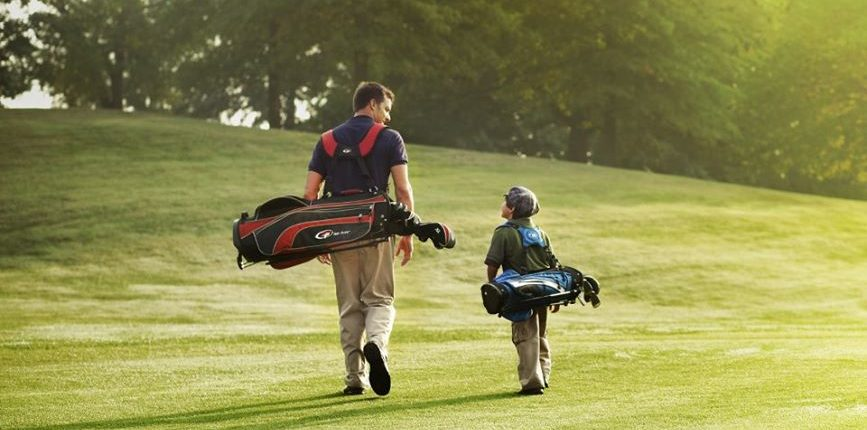 Father and Son walk on golf course with golf clubs slung over their shoulders