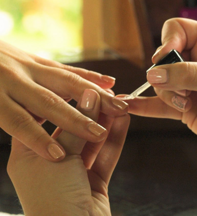 aesthetician's hand applying nail polish to the client's nails