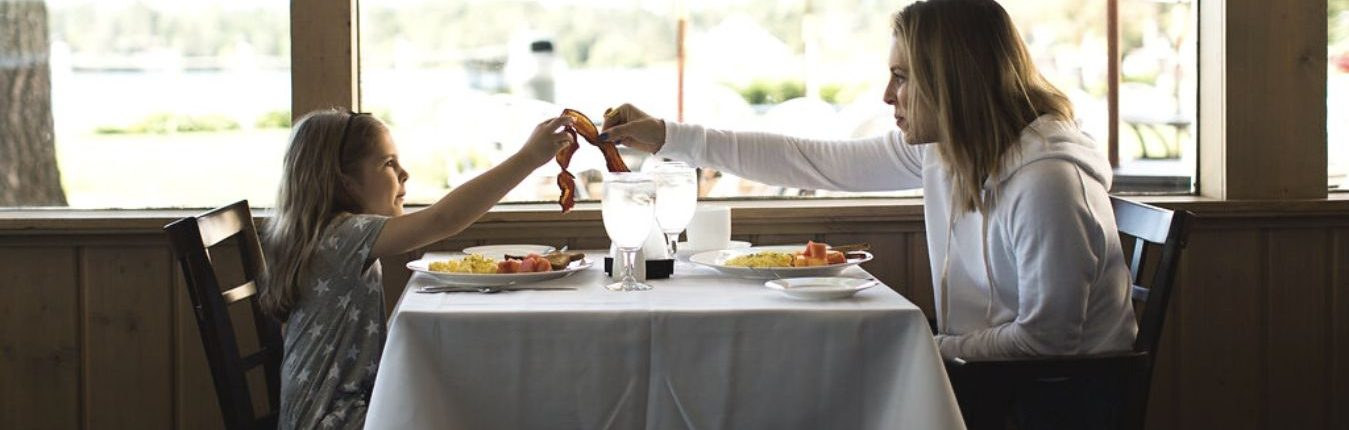 A mother and child splitting a bacon during breakfast at the Madden's Resort.