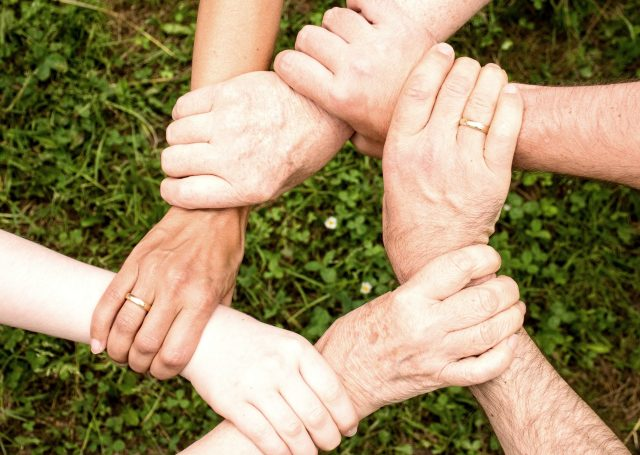 All hands holding the wrists in the outdoors.