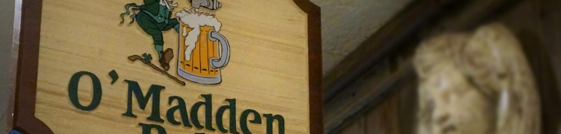 Closeup of the O'madden's pub wooden signage at the entrance of the pub