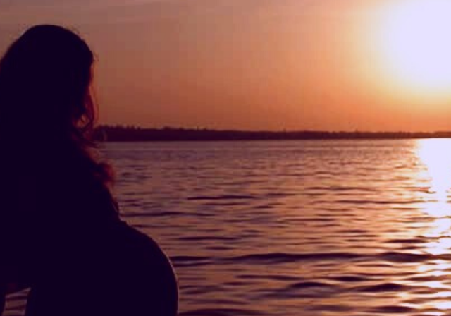 A man and pregnant wife watching the sunset on water