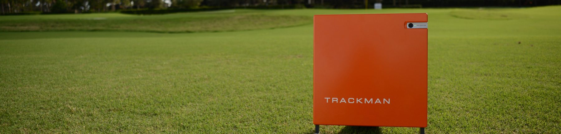 A Trackman golf tracker device placed on the grass.