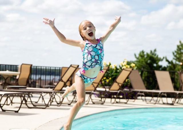A girl jumping into the pool