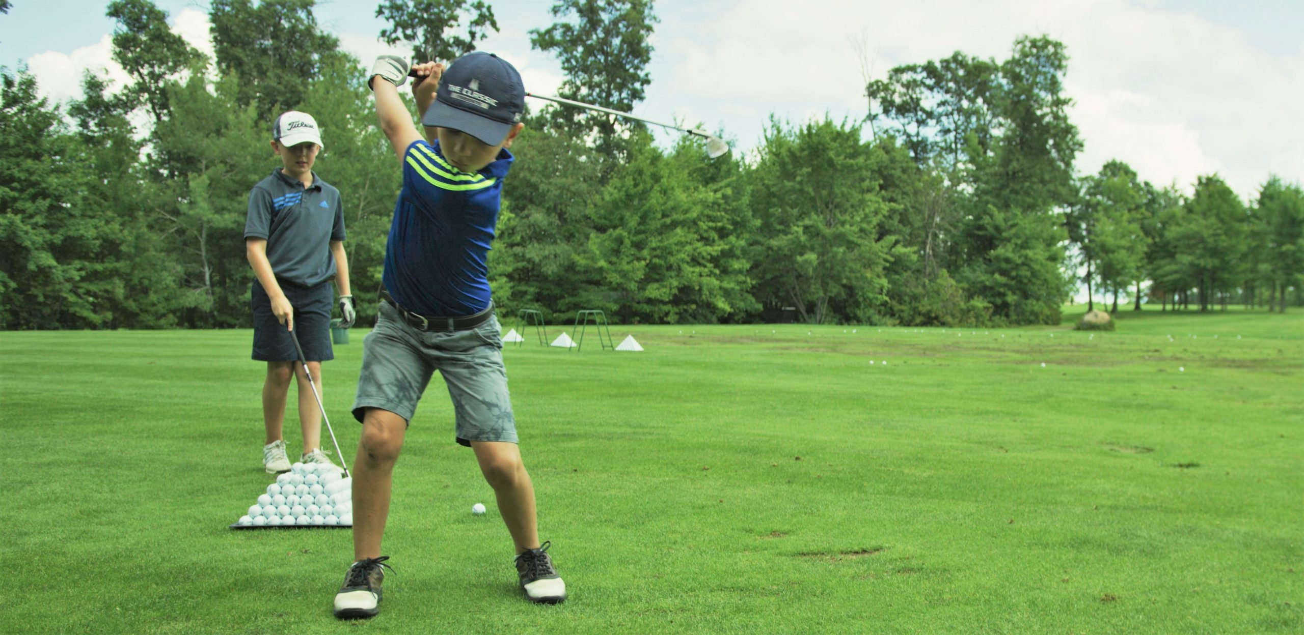A boy swinging golf club as another boy looks on