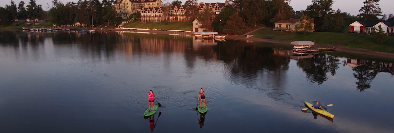 Two women paddleboarding next to a man kayaking on the Gull lake infront of the Madden's Resort building.