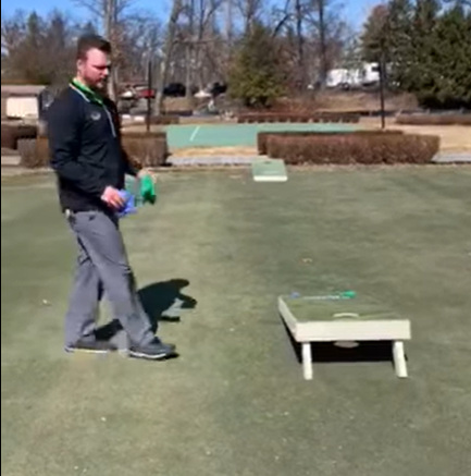 A man walking up to the cornhole game