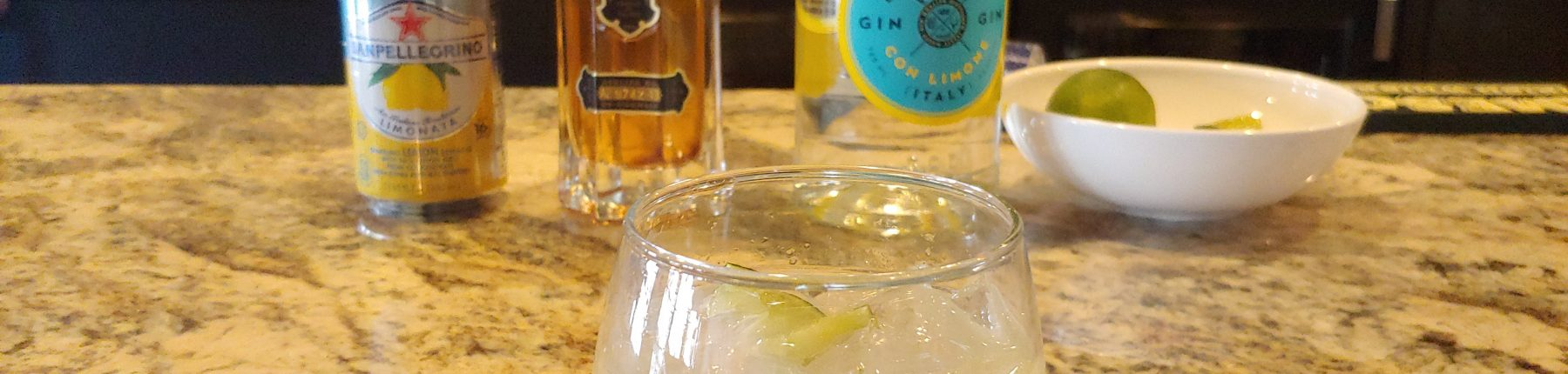 A cocktail placed in front of a can of lemonade, a St. Germain liquor bottle and a bottle of gin