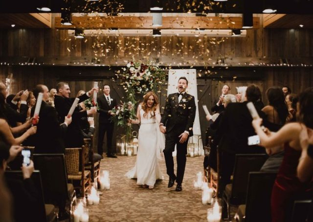 Bride and groom walking hand in hand as guests use confetti poppers on them