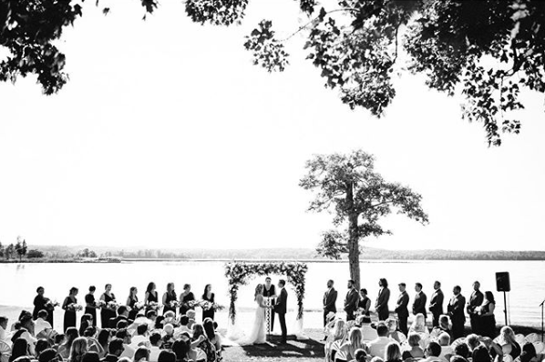 A black and white shot of guests looking on to the bride and groom at the aisle next to the bridesmaids and groomsmen.