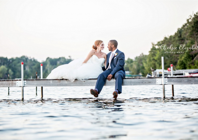 Bride and groom seating on the dock