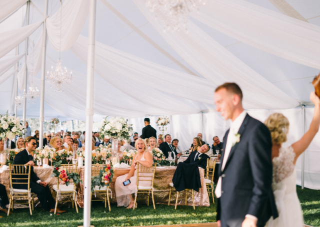 White tent wedding with guests seated on the dining table and looking on to the bride and groom