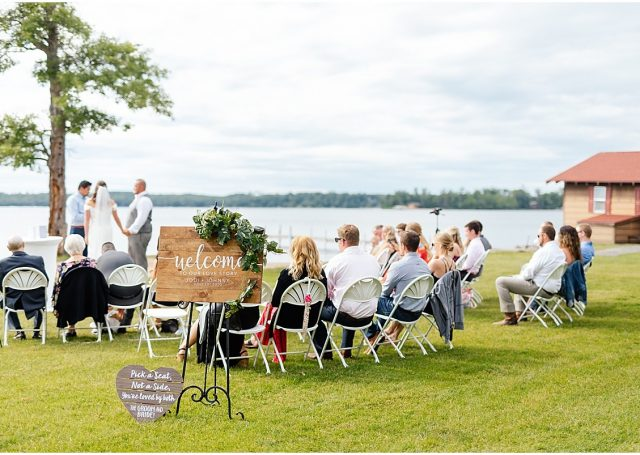 Seated guests looking at the bride and groom taking their vows next to the Gull Lake.
