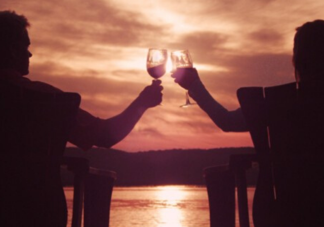 A couple clinking their wine glasses to cheers to the sunset by the water.