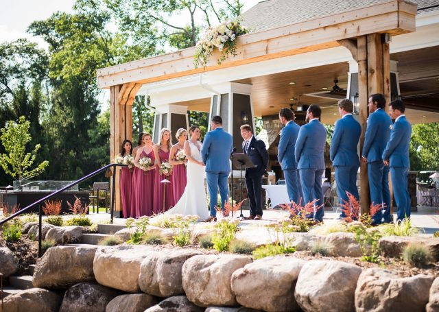 Bride and groom taking their vows in the outdoors next to their bridesmaids and groomsmen.