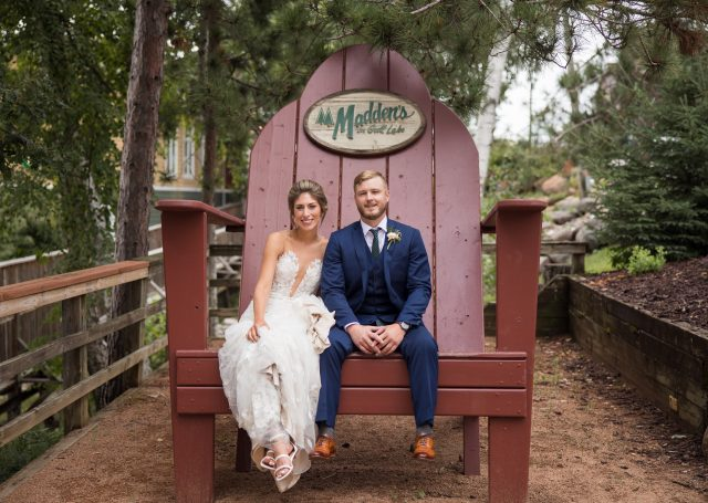 Bride and Groom sitting on a large wooden patio chair near The Pavilion building.