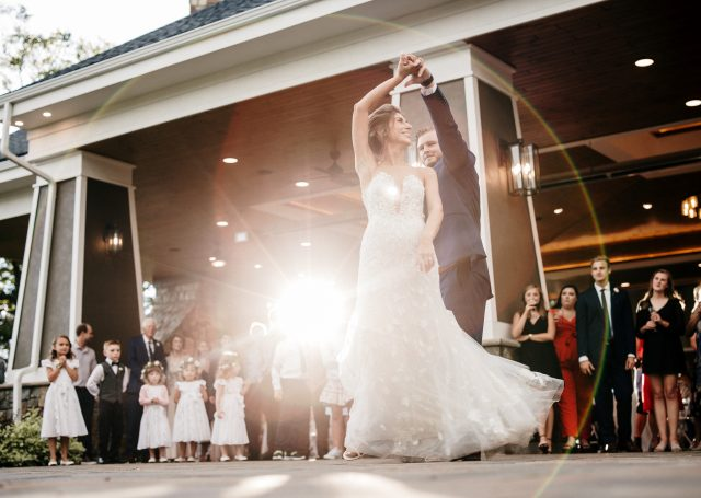 Bride and groom first dance as guests look on