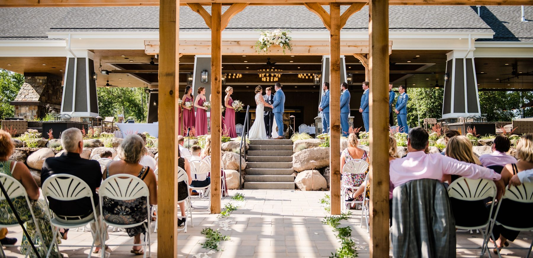 Seated guests looking at the bride and groom taking their vows next to the bridesmaids and groomsmen at The Pavilion
