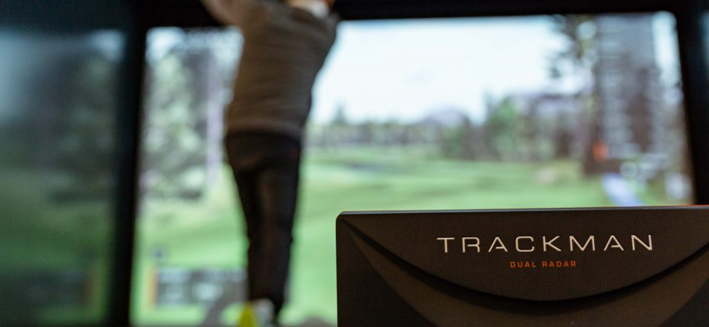 Rear view of a man swinging the golf club next to the Trackman dual radar