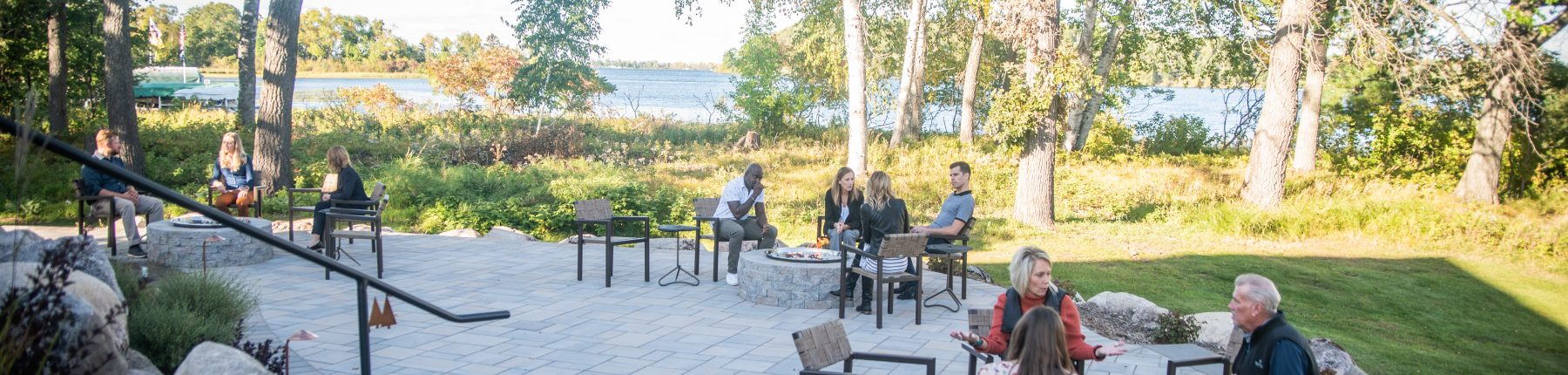 Guests sitting on the patio chairs next to the firepit at Madden's on Gull Lake.