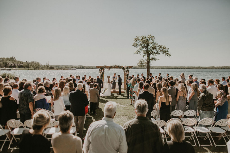 Wedding guests standing up to honor the bride and groom at the aisle