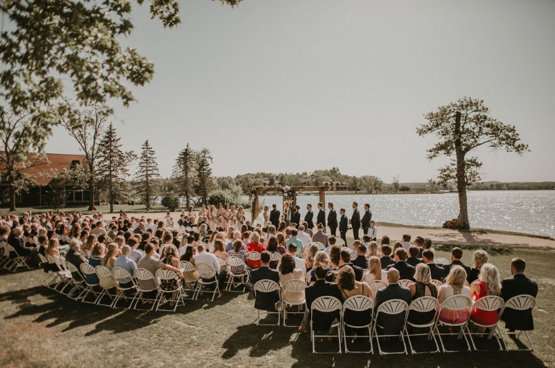 back shot of wedding guests sitting and watching the bride and groom at the aisle