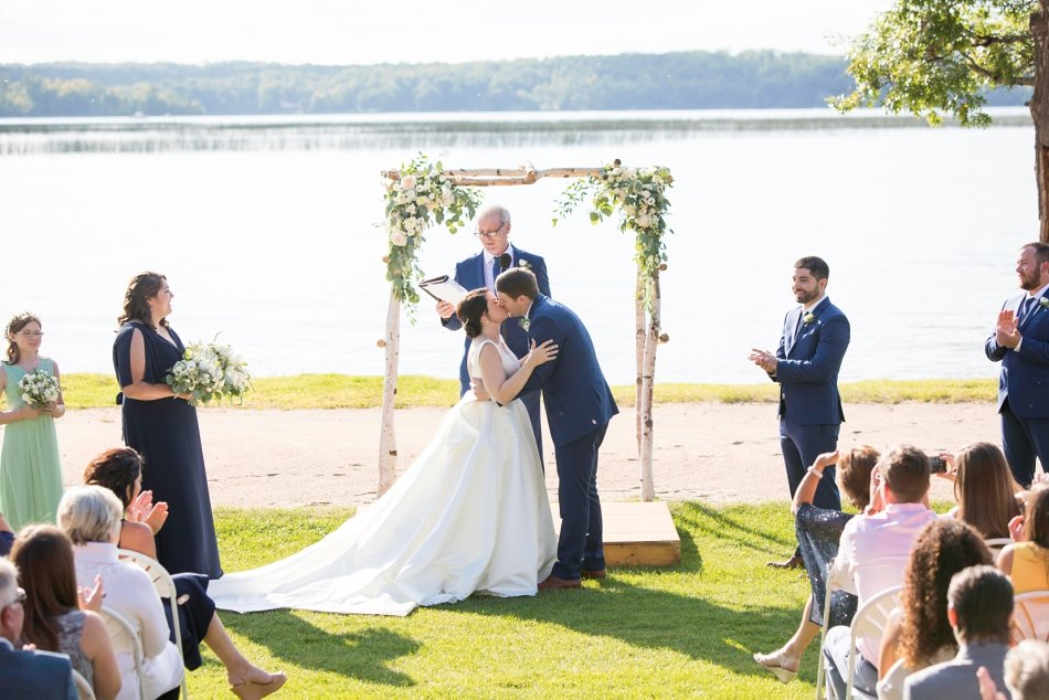 Bride and groom share a kiss as the guest cheer on