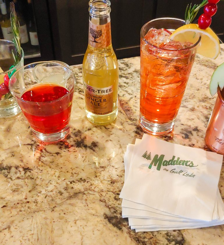 Cocktails next to a bottle of ginger ale placed on a marble counter with Madden's napkins