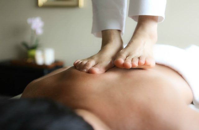 A man lying on his front and receiving ashiatsu massage from the therapist's feet