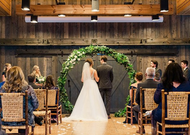 Rearview of a brides and groom at the aisle as seated guests look on