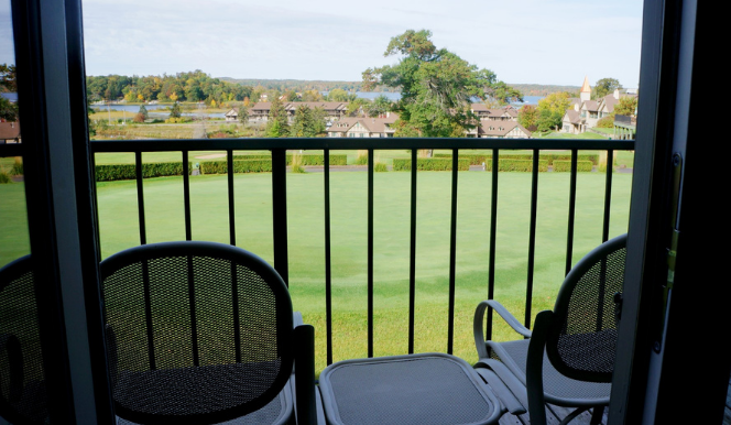 two chairs on a balcony face a green lawn