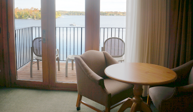 chair and table in hotel room looking out to balcony